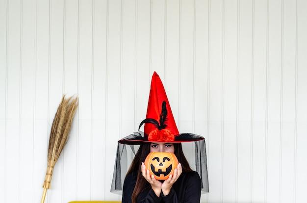Halloween hexe mit einem magischen kürbis,