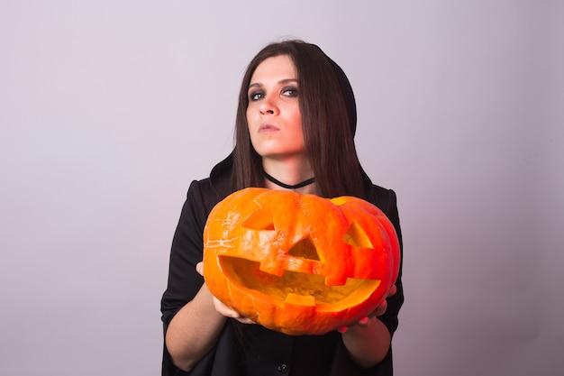 Halloween-hexe mit einem orangefarbenen kürbis jack o lantern