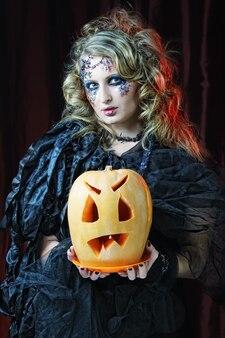 Halloween-hexe mit geschnitztem kürbis über roten vorhängen