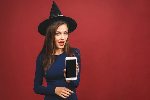 Halloween-hexe mit handy-bildschirm - lokalisiert auf rotem hintergrund. emotionale junge frau im halloween-kostüm.
