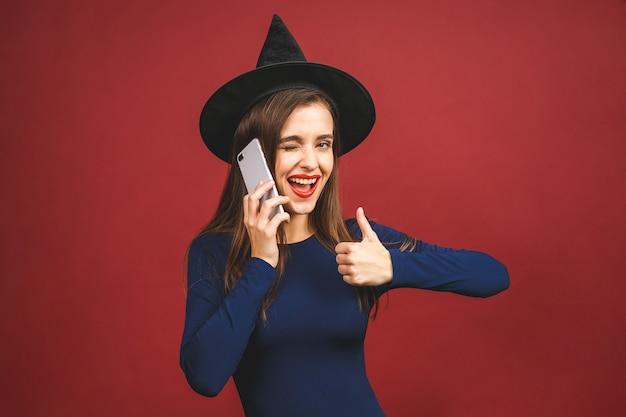 Halloween-hexe mit handy - lokalisiert auf rotem hintergrund. emotionale junge frau im halloween-kostüm. smartphone benutzen.