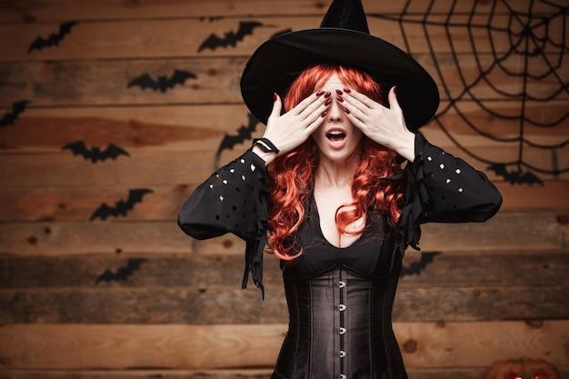 Halloween-hexekonzept - glückliches halloween-rotes haar hexe, die hände hält, schließen die augen, die über altem hölzernem studiohintergrund aufwerfen.