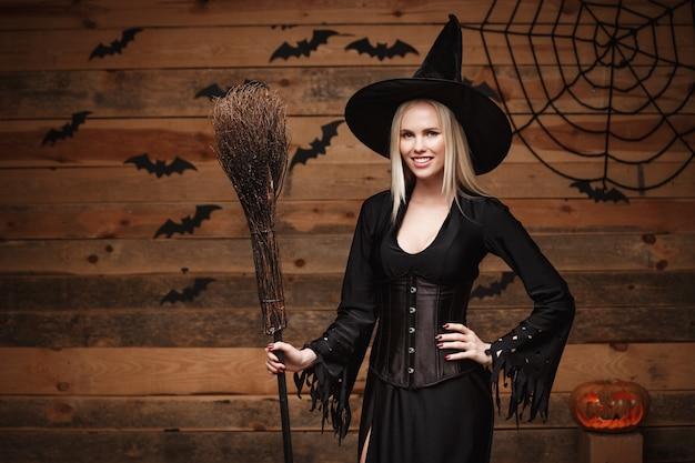 Halloween-hexekonzept - glückliches halloween sexy hexe, die über altem hölzernem studiohintergrund aufwirft.