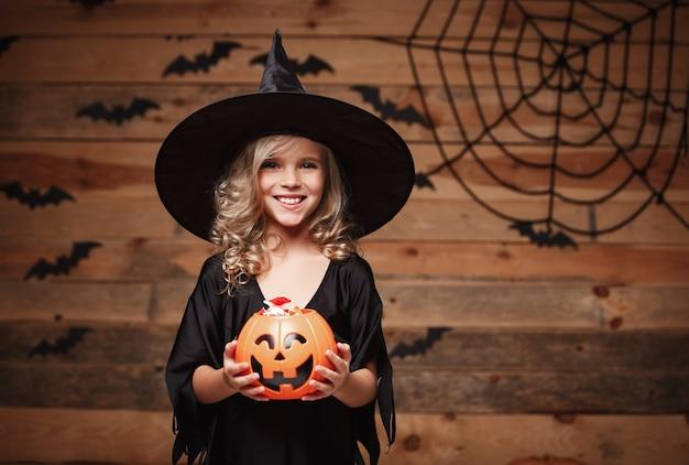 Halloween-hexekonzept - kleines kaukasisches hexenkind genießen mit halloween-süßigkeitskürbiskar. über fledermaus und spinnennetz hintergrund.
