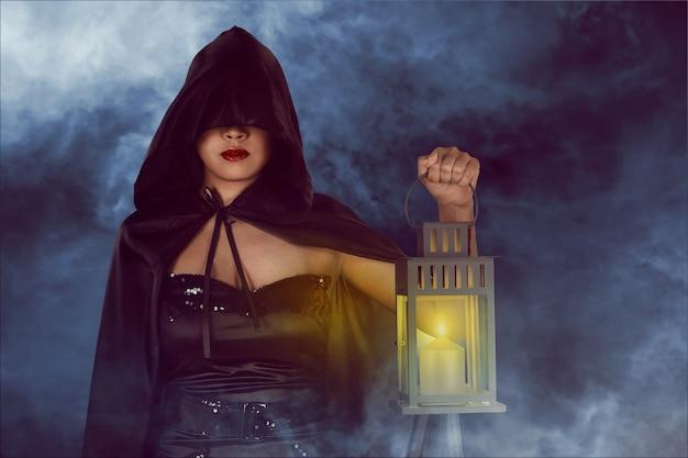 Halloween-hexenfrau, die laterne hält