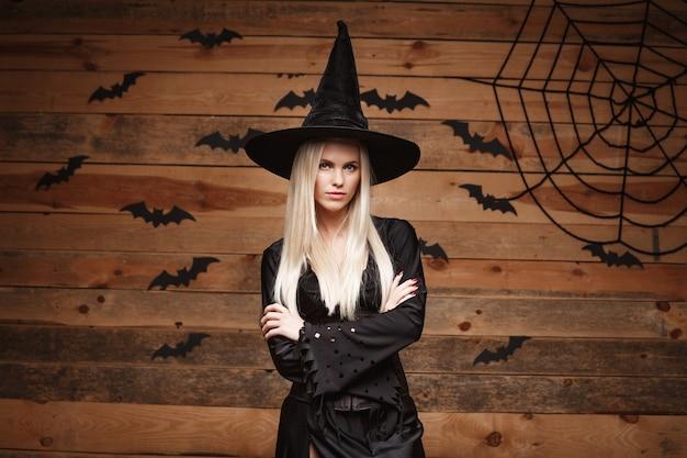 Halloween-hexenkonzept - glückliche halloween-hexe, die kreuzende arme hält, die über alte holzwand aufwerfen.