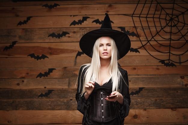 Halloween-hexenkonzept - glückliche halloween-hexe, die mit smartphone über alter holzwand posiert.