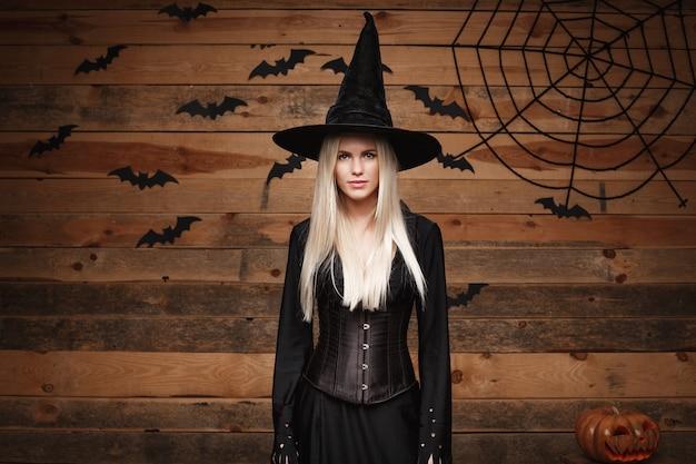 Halloween-hexenkonzept glückliche halloween-sexy hexe, die über altem hölzernem studiohintergrund posiert
