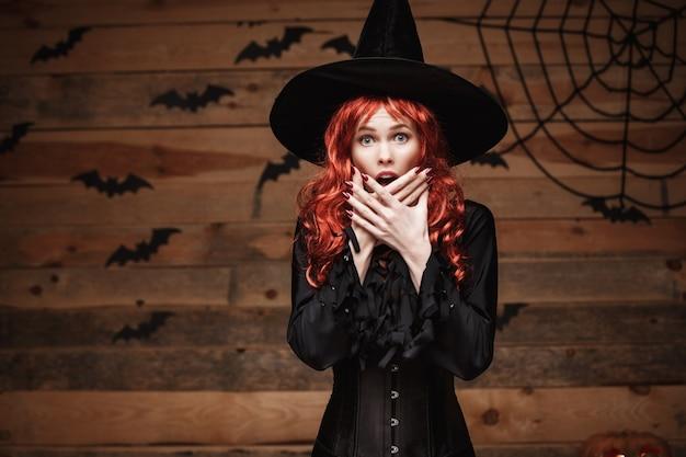 Halloween hexenkonzept - glückliches halloween-rotes haar hexe, die mit entsetztem gesicht über altem hölzernem studiohintergrund aufwirft.