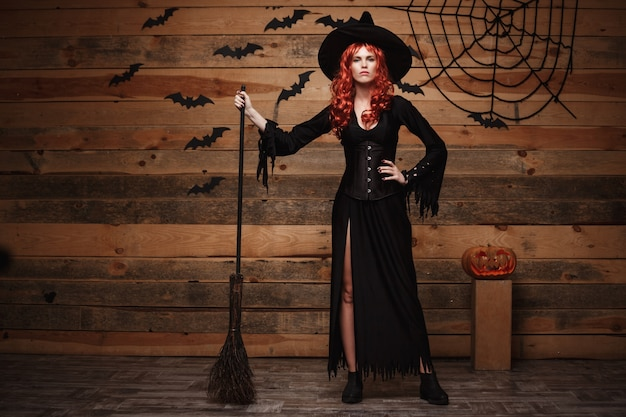 Halloween hexenkonzept - glückliches halloween-rotes haar hexe, die mit magischem besenstiel über altem hölzernem studiohintergrund aufwirft.