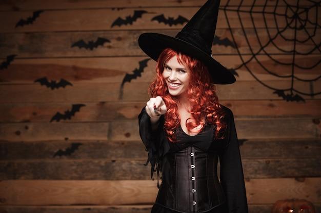 Halloween hexenkonzept - glückliches halloween-rotes haar hexe, die mit magischem stab über altem hölzernem studiohintergrund aufwirft.