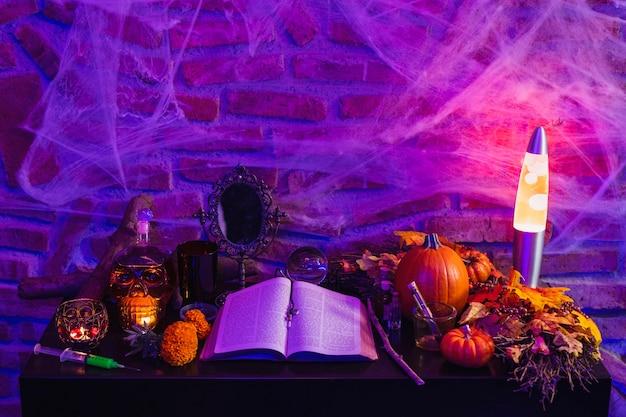 Halloween hexentisch, altar mit magischen gegenständen, antikes buch für einen zauber, brennende kerzen und kürbis