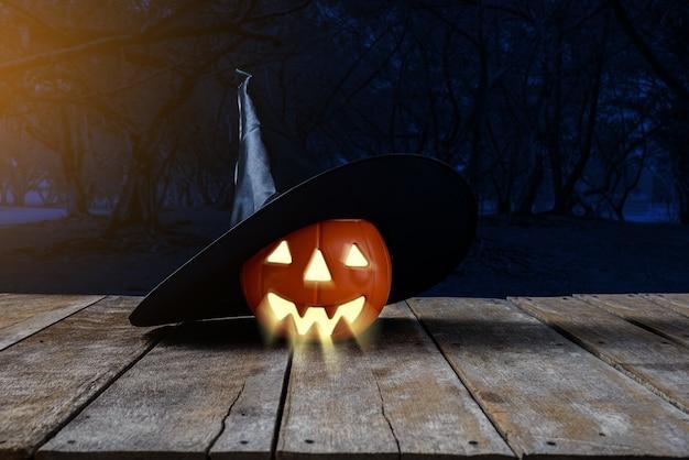 Halloween-hintergrund. gespenstischer kürbis, hexenhut auf bretterboden mit mond und dunklem wald