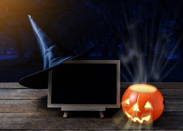 Halloween-hintergrund. gespenstischer kürbis, hexenhut, tafel auf bretterboden und dunkle vorderteile