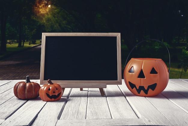 Halloween-hintergrund. gespenstischer kürbis, tafel auf bretterboden und dunkler wald. hallowee