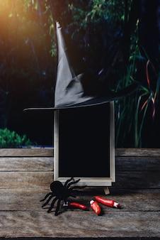 Halloween-hintergrund. hexenhut, schwarze spinne, tafel auf bretterboden und dunkler wald