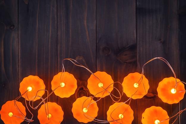 Halloween-hintergrund, kürbis-lichterketten auf holztisch