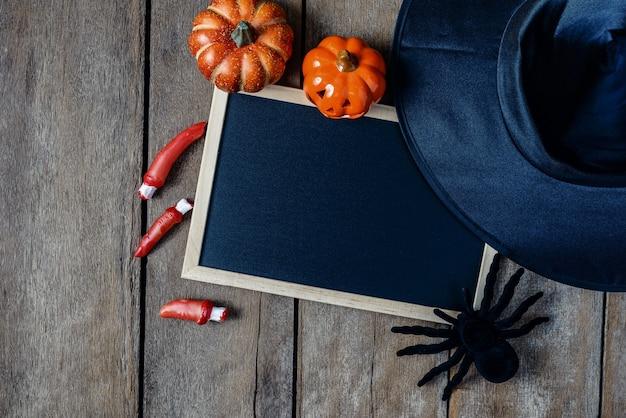 Halloween-hintergrund mit kürbisen, hexenhut, schwarzer spinne, fingern und tafel auf woo