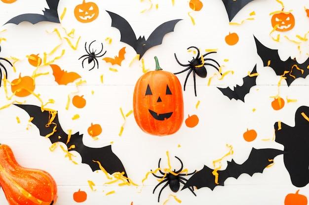 Halloween-hintergrund mit kürbislaterne, kürbissen, papierfledermäusen, spinnen, konfetti auf weißem holzhintergrund. halloween-feiertagsdekorationen. flache lage, ansicht von oben. party einladungsmodell, feier.