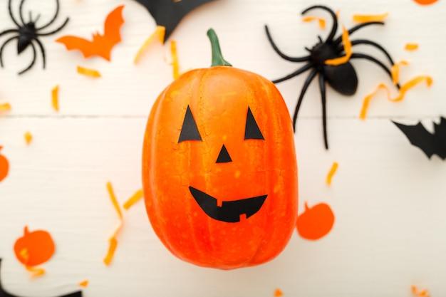Halloween-hintergrund mit kürbislaterne, papierfledermäusen, spinnen, konfetti auf weißem hintergrund aus holz. halloween-feiertagsdekorationen. flache lage, ansicht von oben. party einladungsmodell, feier.