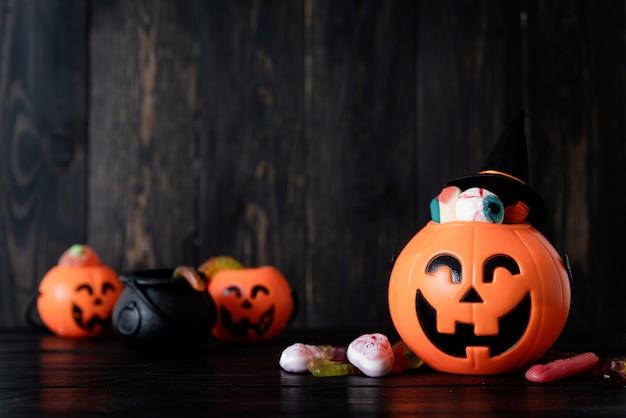 Halloween-hintergrund mit kürbislaternenkürbissen mit süßigkeiten auf schwarzem holzhintergrund