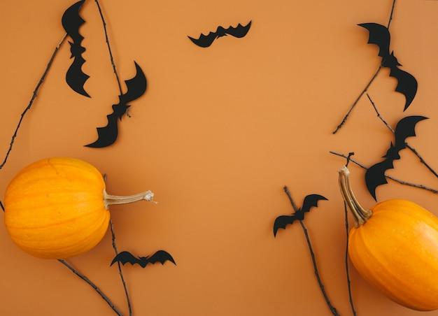 Halloween hintergrund mit kürbissen, fledermäusen, dekorationen auf orange hintergrund. halloween-partyeinladungskartenmodell mit kopienraum.