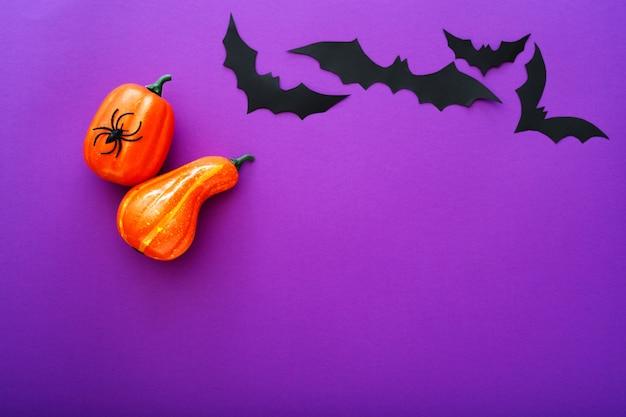 Halloween-hintergrund mit kürbissen, spinnen und schwarzen papierfledermäusen, die über lila hintergrund fliegen. platz kopieren. halloween und dekorationskonzept.
