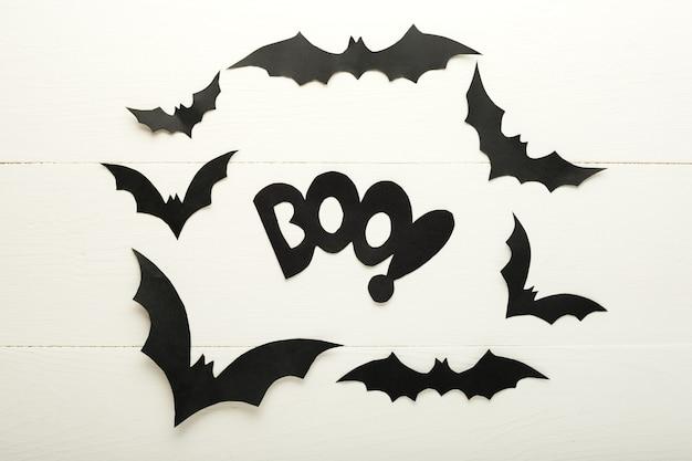 Halloween-hintergrund mit papierfledermäusen und boo-schriftzug auf weißem hintergrund aus holz. halloween-feiertagsdekorationen. flache lage, ansicht von oben, kopienraum. party einladungsmodell, feier.