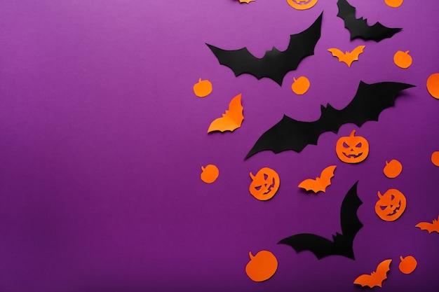 Halloween hintergrund mit papierkürbissen, jack o laterne schwarz orange fledermäuse fliegen über lila hintergrund, kopie raum