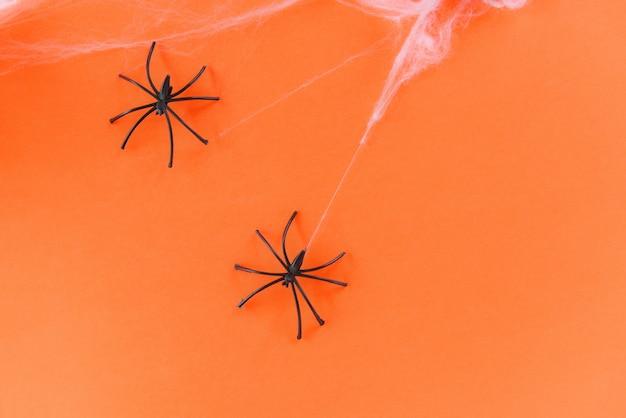 Halloween-hintergrund mit spinnennetz und schwarzer spinne an den orange dekorationsfeiertagen festlich für parteizubehör