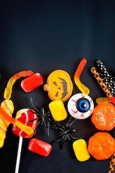 Halloween-hintergrund mit vielen kürbis-, süßigkeitenaugen und spinnen
