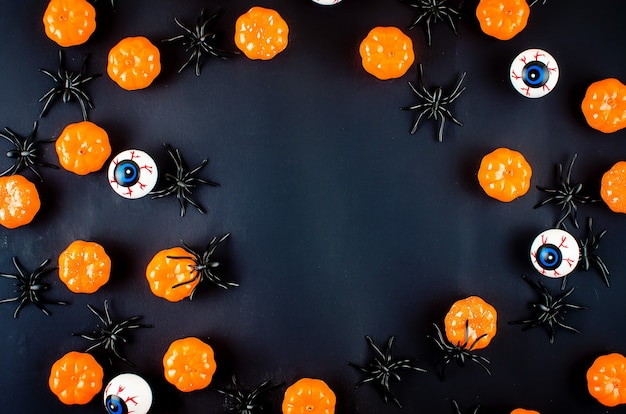 Halloween-hintergrund mit vielen kürbis-, süßigkeitsaugen und spinnen auf schwarzem, herbstferienkonzept, ernte, kopienraum, draufsicht, modellock