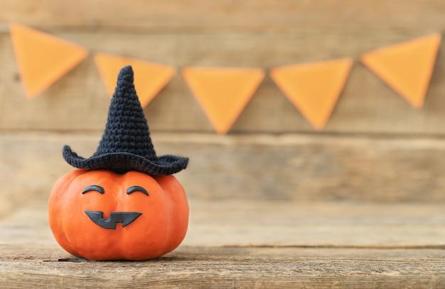 Halloween-hintergrund von kürbis im schwarzen hut mit lustigem gesicht auf einer hölzernen feiertagsoberfläche