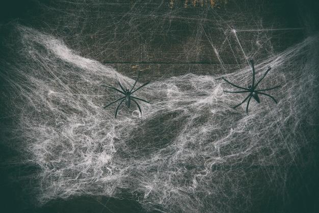 Halloween-horrordekorations-spinnennetz und schwarze spinne auf hölzerner dunkelheit