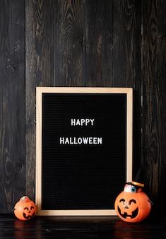 Halloween jack o laternen kürbisse mit süßigkeiten auf schwarzem holzhintergrund briefbrett mit wörtern ha...