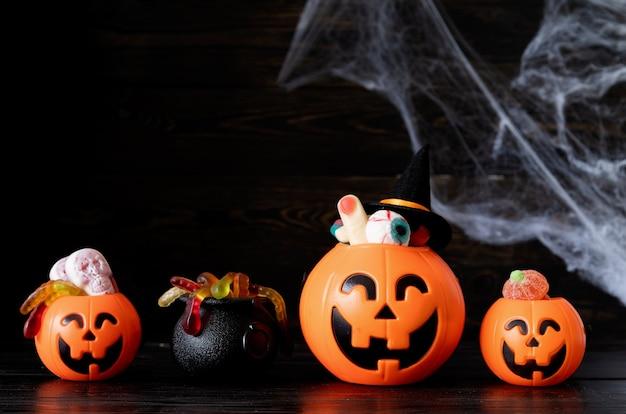 Halloween jack o laternen kürbisse mit süßigkeiten auf schwarzem holzhintergrund mit spinnennetz