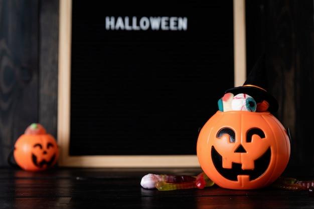 Halloween jack o laternen kürbisse mit süßigkeiten auf schwarzem holzhintergrund verschwommenes briefbrett mit ...