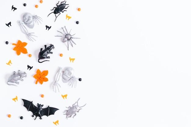Halloween-karte auf weißem hintergrund mit schwarzem und silbernem feiertagsdekor. schwarzer kegel mit silbernen und schwarzen fledermäusen und herumfliegenden geistern, kopierraum, draufsicht