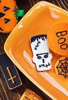 Halloween-kekse auf orangefarbenem teller