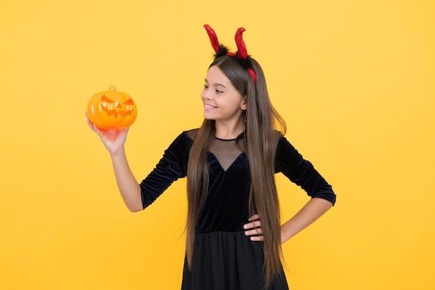 Halloween-kind in roten wichtelhörnern, die trick-o-leckerei mit kürbis-jack-o-laterne, halloween-jack-o-laterne spielen.