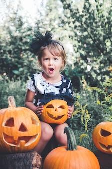 Halloween. kind in schwarzer kleidung mit jack-o-laterne in der hand, süßes oder saures.