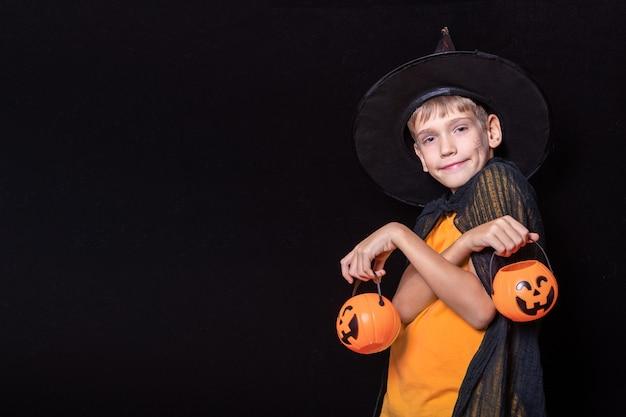 Halloween-kinder. junge in zauberhut und orangefarbenem t-shirt, das halloween-kürbis-förmige eimer mit süßigkeiten auf schwarzem hintergrund hält. bereit für das süßes oder saures im urlaub.