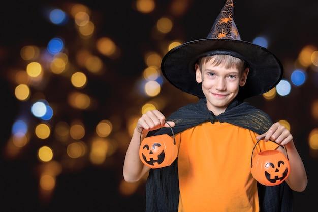 Halloween-kinder. junge in zauberhut und orangefarbenem t-shirt, das halloween-kürbis-förmige eimer mit süßigkeiten vor einem schwarzen hintergrund mit hellem bokeh hält. bereit für den süßes oder saures urlaub.