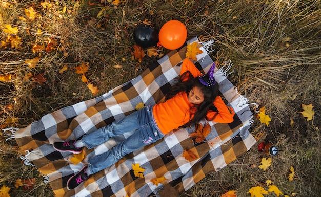 Halloween-kinder. lächelndes mädchen des porträts mit dem braunen haar, das auf decke legt. lustige kinder in karnevalskostümen im freien.