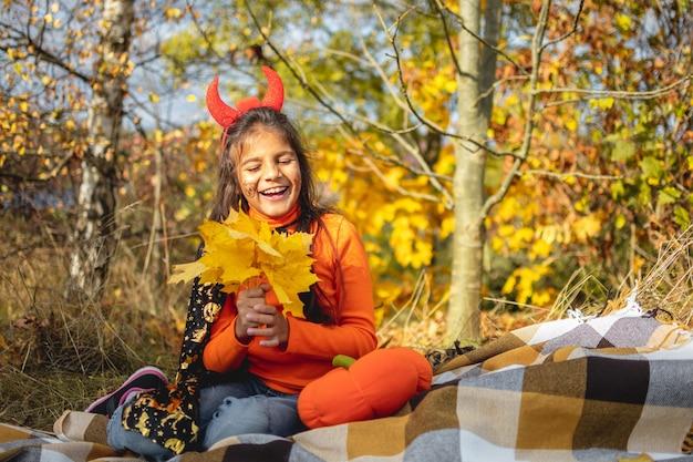 Halloween-kinder. lächelndes mädchen des porträts mit dem braunen haar, das auf decke legt. lustige kinder in karnevalskostümen.