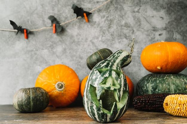 Halloween-komposition mit grünem kürbis und fledermäusen