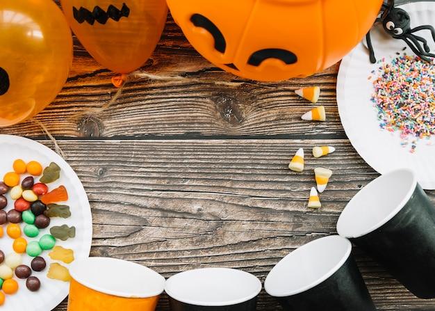 Halloween-komposition mit pappbecher und süßigkeiten