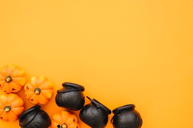 Halloween-komposition mit teekannen und kürbissen