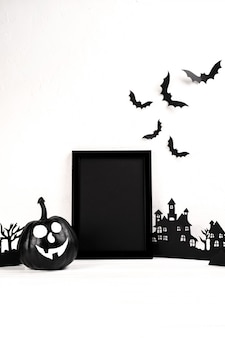 Halloween-komposition. schwarzer fotorahmen und verlassenes dorf der papierkunst, kürbis auf weiß.