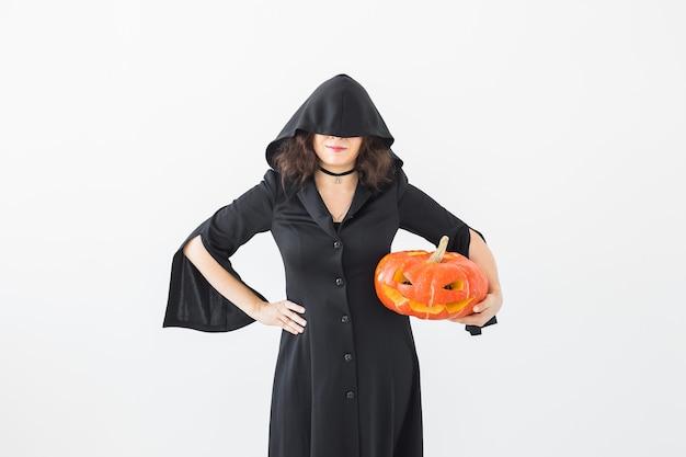 Halloween-konzept - anonyme hexe mit kürbis-kürbislaterne auf heller wand